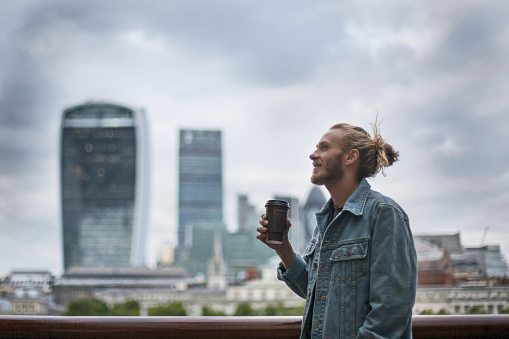 Pensive hipster drinking coffee in the street at London