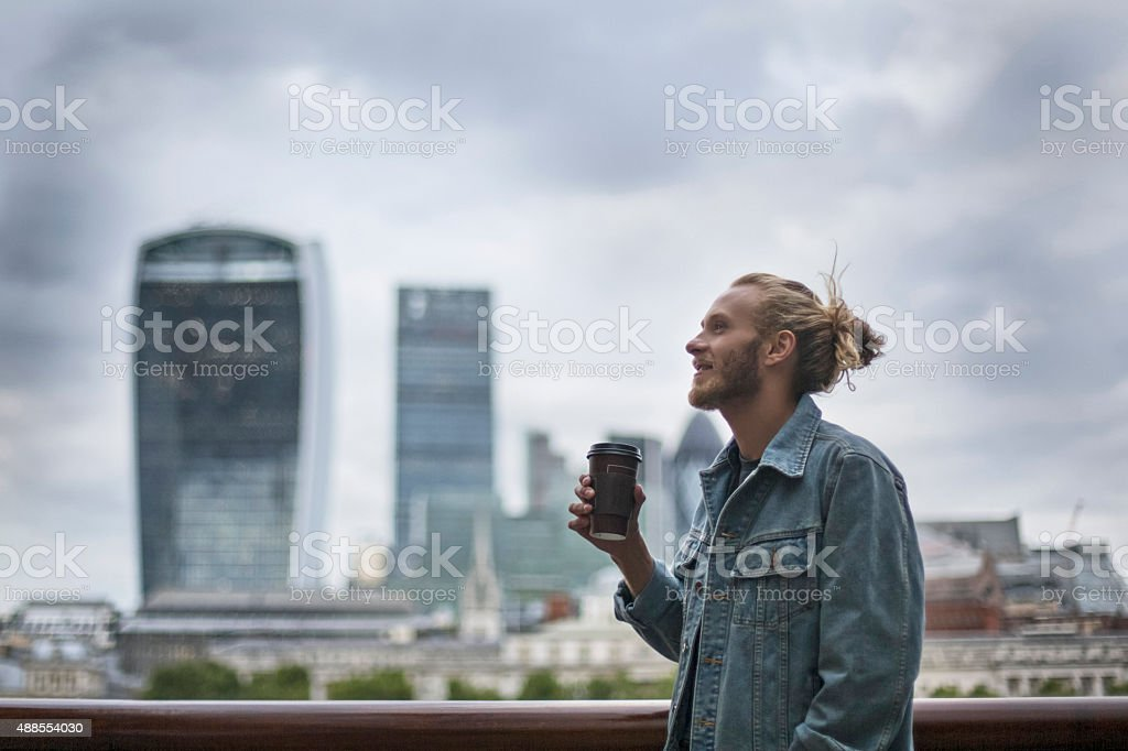 Pensive hipster drinking coffee in the street at London stock photo