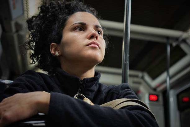 Pensive Hispanic young woman traveling in the subway stock photo