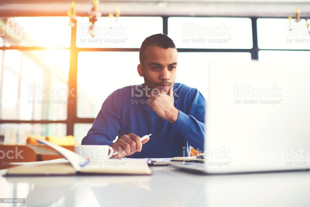 Pensive international afro american student watching training webinar on laptop computer improving skills and knowledge, concentrated dark skinned freelancer pondering on completing working tasks stock photo