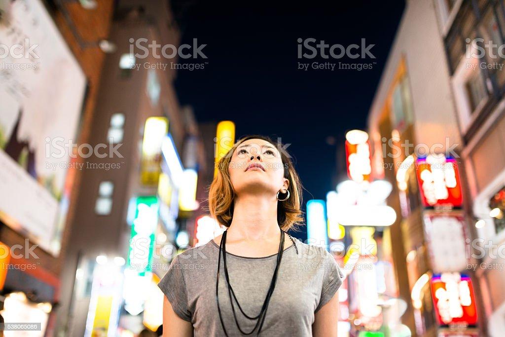 pensive japanese woman enjoy the night in tokyo stock photo