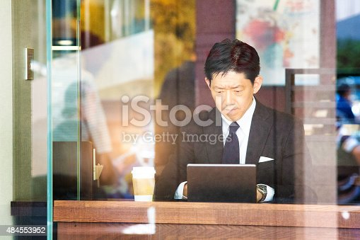 istock Pensive Japanese writer in cafe typing seriously on laptop 484553952