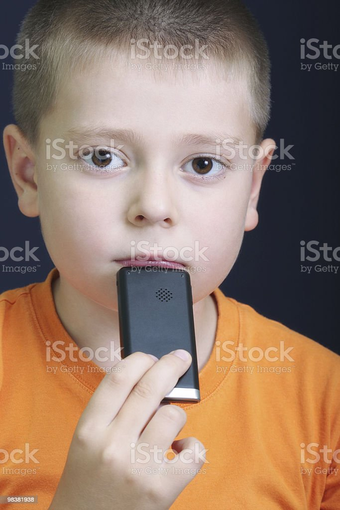 Pensive kid in orange with cellphone royalty-free stock photo