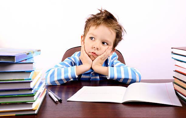 Nachdenklich kleine Junge sitzend am Schreibtisch – Foto