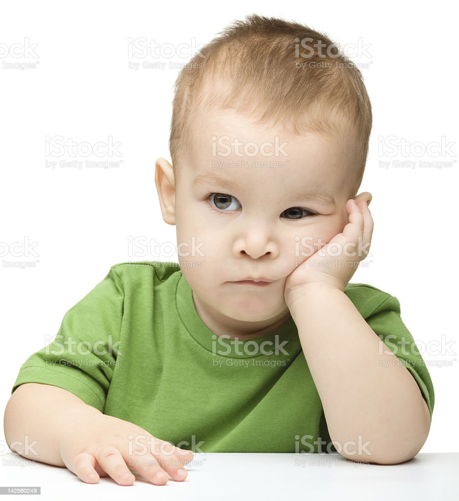 Pensive little boy support his head with hand royalty-free stock photo