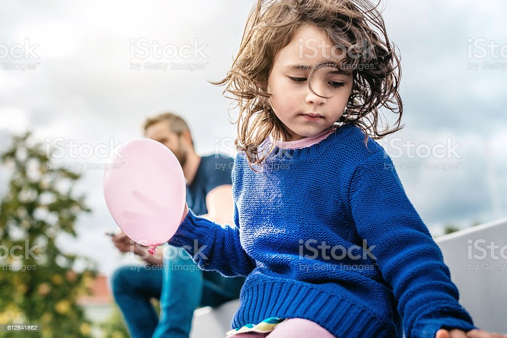 pensive little girl holding pink balloon while father using mobile stock photo