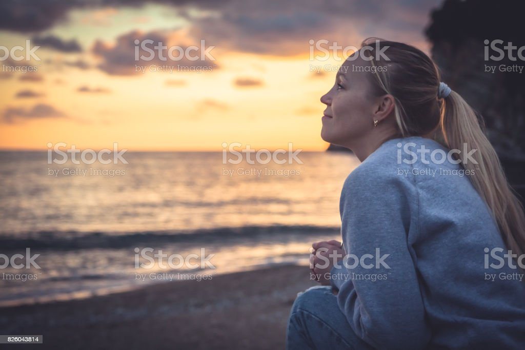 Pensive lonely smiling woman looking with hope into horizon during sunset at beach stock photo