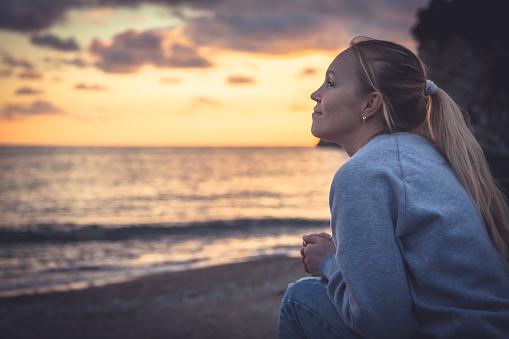 Pensive Lonely Smiling Woman Looking With Hope Into Horizon During Sunset At Beach - zdjęcia stockowe i więcej obrazów Bez wyrazu