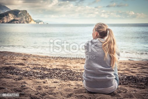 istock Pensive lonely young woman sitting on beach hugging her knees and looking into the distance with hope 664047240