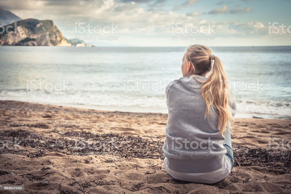 Pensive lonely young woman sitting on beach hugging her knees and looking into the distance with hope stock photo