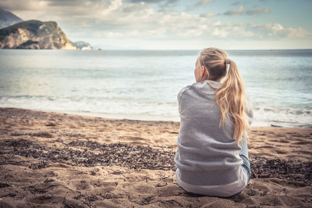 pensive lonely young woman sitting on beach hugging her knees and looking into the distance with hope - sitting stock pictures, royalty-free photos & images