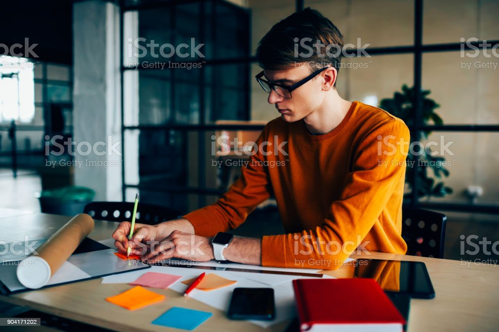 Pensive male engineer drafting sitting at working place with equipment making notes of ideas on colorful stickers, skilled architect planning project creating strategy and making drawings in office stock photo