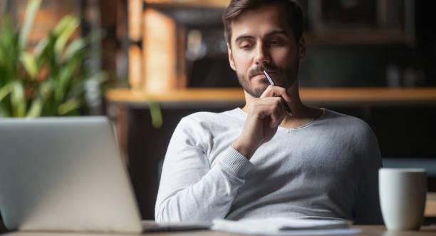 Pensativo hombre pensando en la solución de problemas que funciona en la computadora portátil - foto de stock