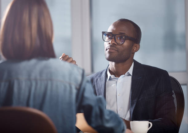Pensive man is thinking about new project Source of inspiration. Wistful young professional african manager in glasses is working in office with colleague female who sitting in front of him. He is looking aside thoughtfully qualification round stock pictures, royalty-free photos & images