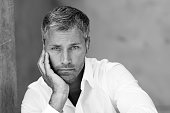 An attractive masculine man with grey hair looking pensive. He is leaning sideways on one hand staring at the camera. He is wearing a white button down shirt with open collar. The black and white image was shot outdoors. There is some copy space on the top of the right side.