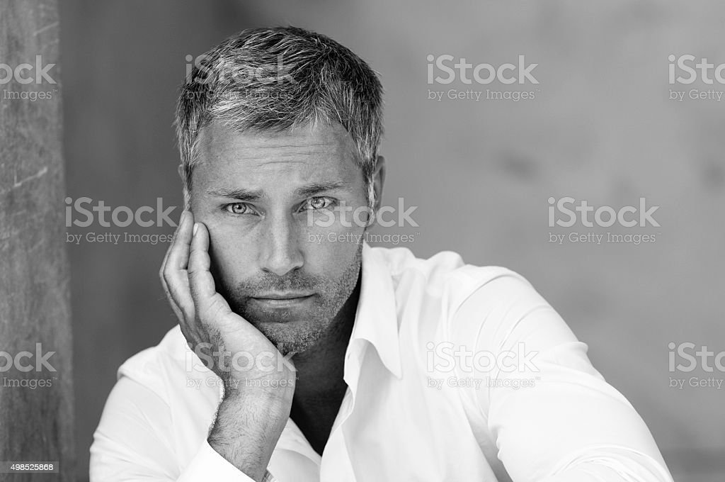 pensive man leaning on his hand stock photo