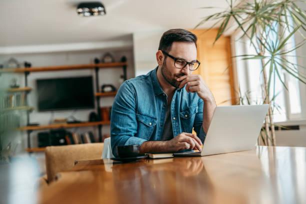 homem pensativo olhando para o laptop enquanto senta na mesa de madeira, retrato. - laptop - fotografias e filmes do acervo