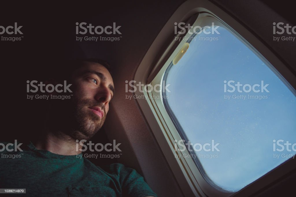 Pensive man looking outside through the window of an airplane.