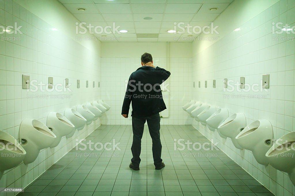Pensive man on the toilet in fluorescent light stock photo