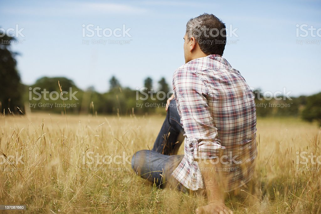 Pensive man sitting in rural field stock photo