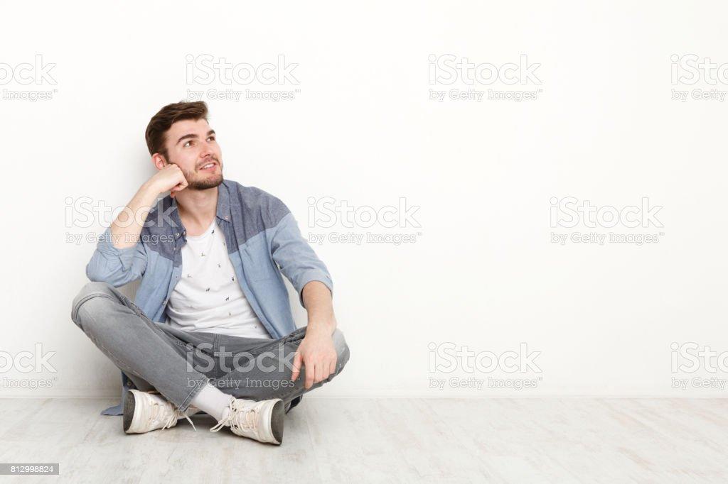 Homme pensif assis sur le sol et regardant vers le haut - Photo