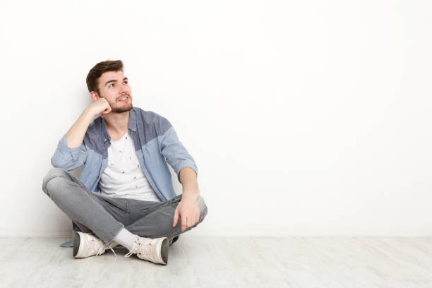 pensive man sitting on floor and looking upwards - sitting on floor stock photos and pictures