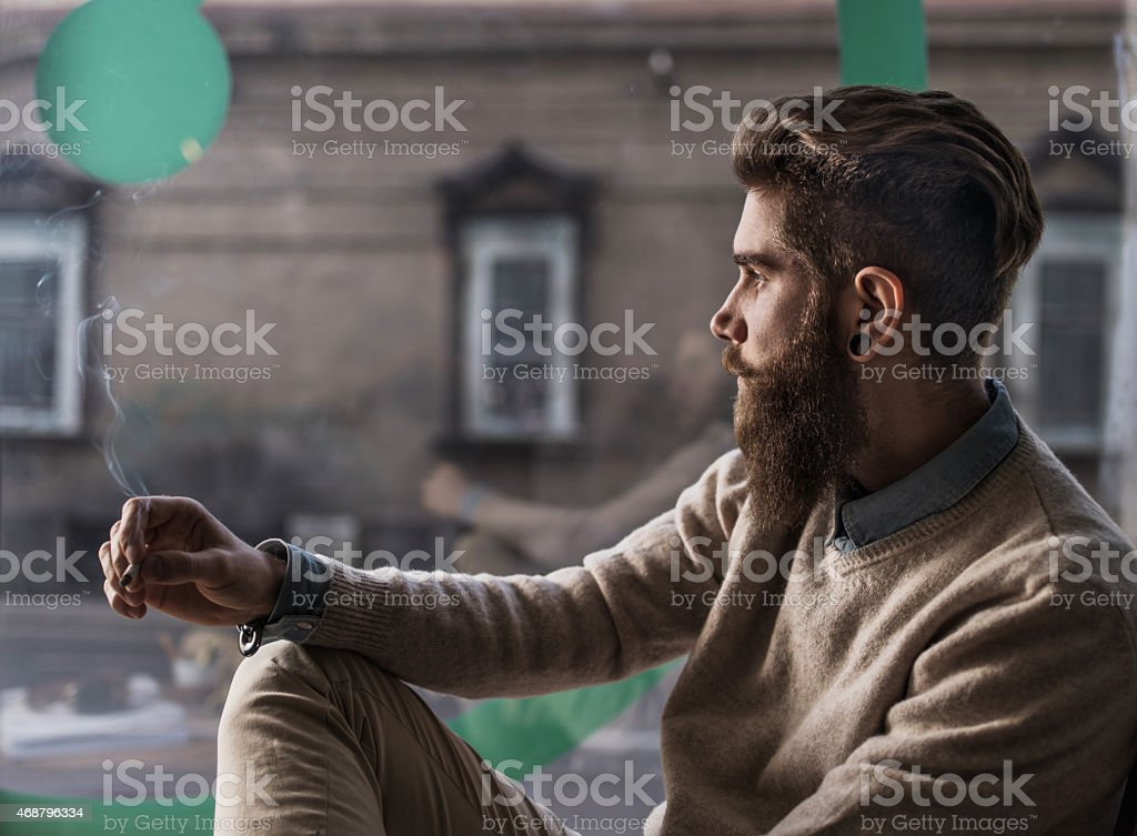 Pensive man with a cigarette looking through window. stock photo
