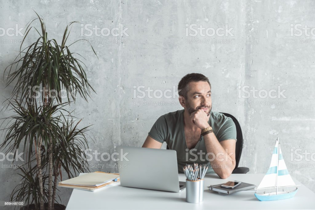 Pensive man with stubble is laboring in office stock photo