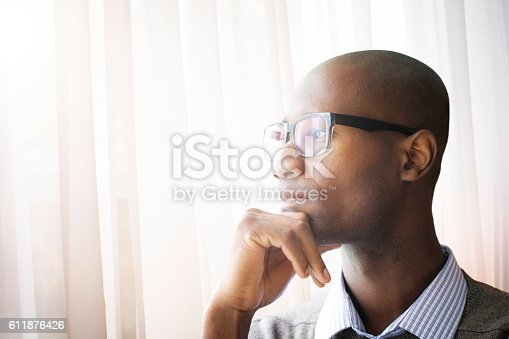 istock Pensive mature bald black man by a window 611876426