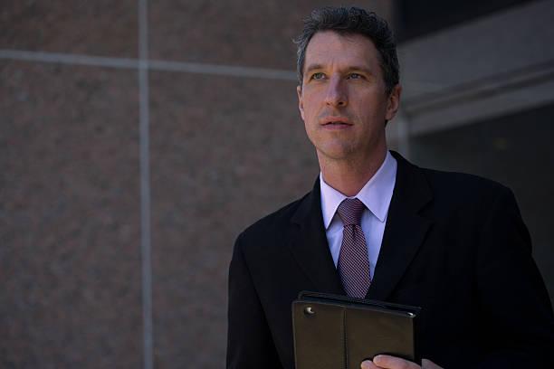 pensive mature businessman outside an office building - foto's van business people on computer stockfoto's en -beelden