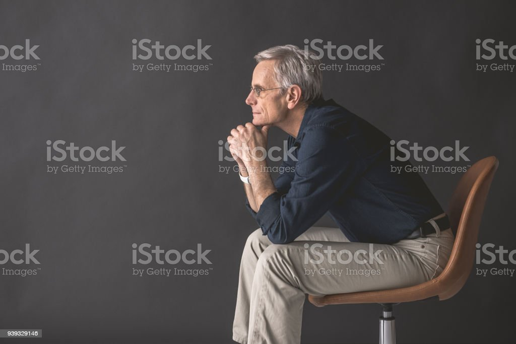 Pensive mature male locating on seat stock photo