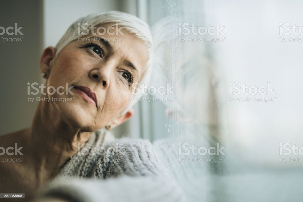 Pensive mature woman day dreaming by the window. stock photo