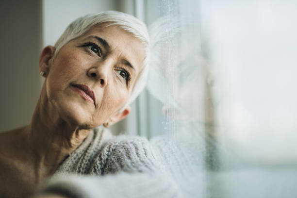 Pensive mature woman day dreaming by the window. Portrait of beautiful senior woman looking through the window during rainy day. Copy space. introspection stock pictures, royalty-free photos & images