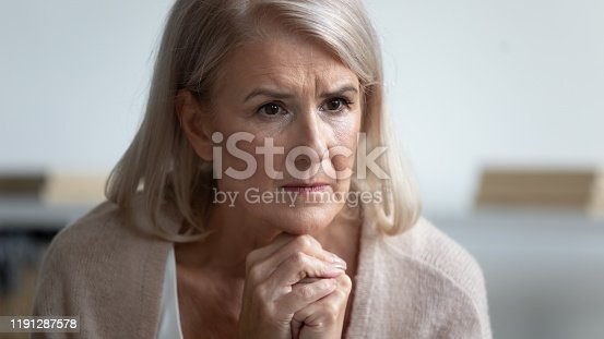 874789168istockphoto Pensive mature woman feels stressed lost in thoughts sitting indoors 1191287578