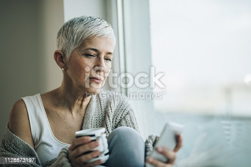 Serious mature woman relaxing by the window and typing a message on her mobile phone. Copy space.