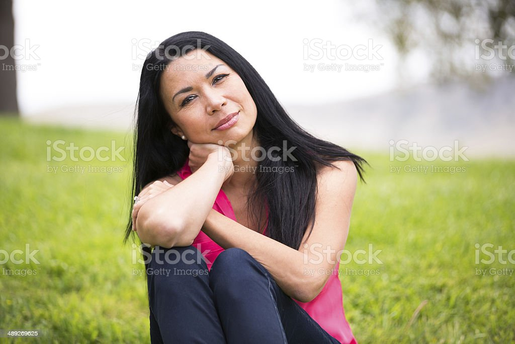 Portrait of a pensive middle age woman of Asian ethnicity.