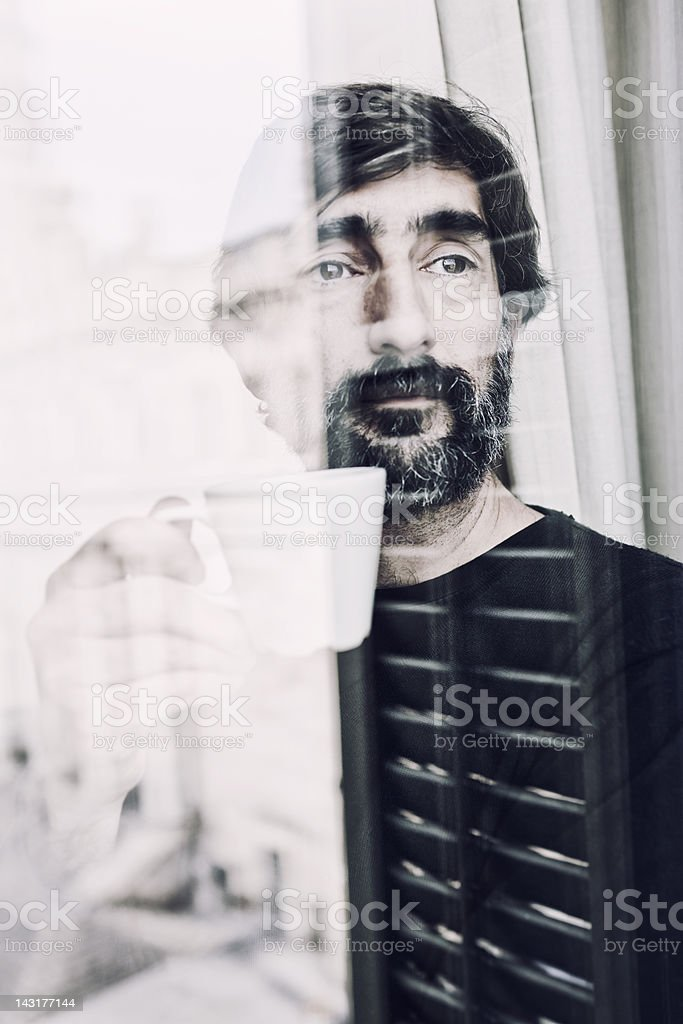 Pensive middle aged man drinking coffee looking through a window stock photo
