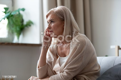 874789168istockphoto Pensive middle-aged woman seated on couch lost in thoughts 1191287581