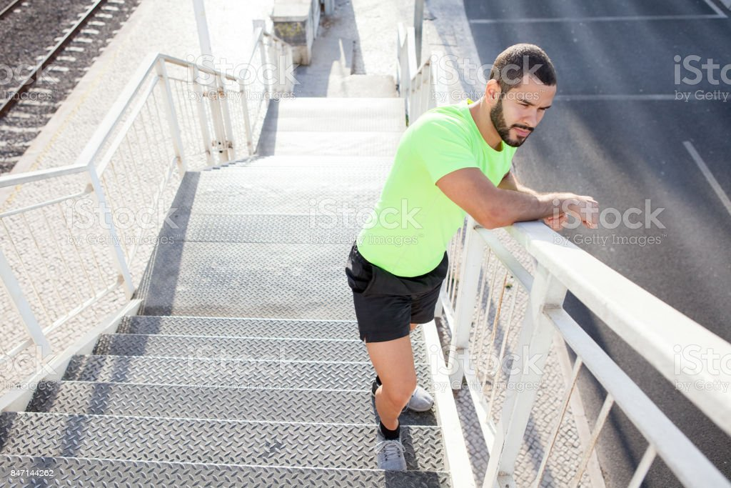 Pensive muscled man standing on staircase stock photo