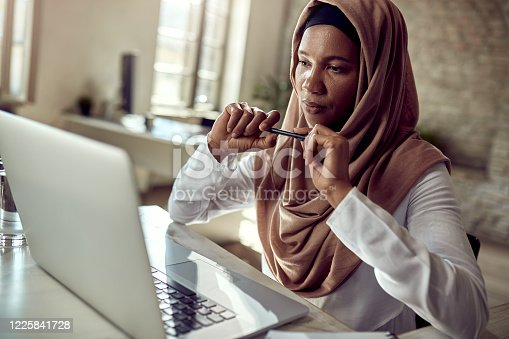 Black Islamic businesswoman reading an e-mail on a computer while working in the office.