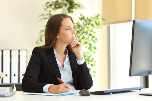 Pensive office worker looks away stock photo