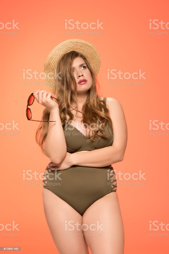 pensive overweight woman in swimsuit stock photo