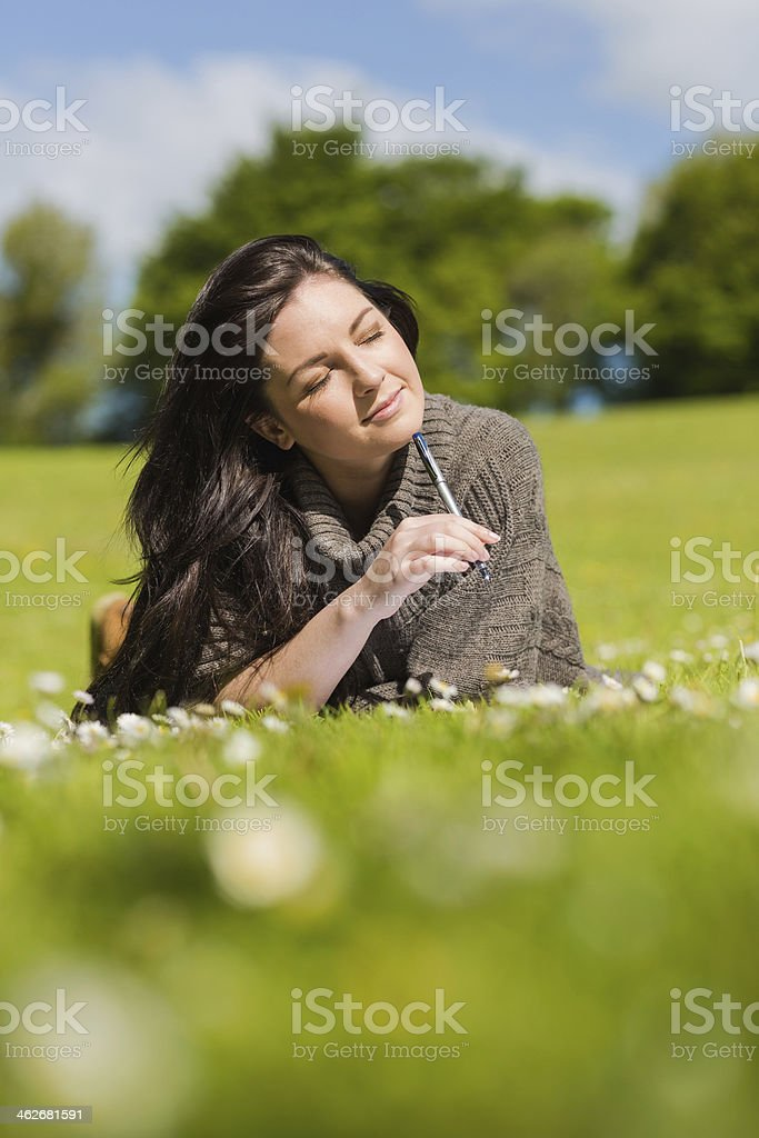 Pensive pretty brunette writing while lying on the grass royalty-free stock photo