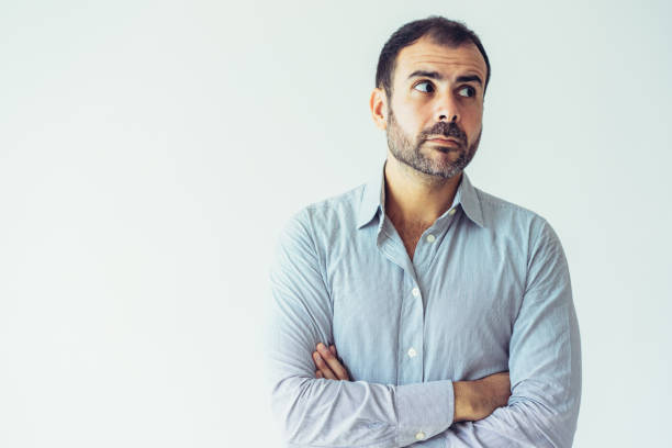 Pensive puzzled Latin man with crossed arms looking aside Pensive puzzled Latin man with crossed arms looking aside. Serious frowning handsome male manager in shirt thinking. Uncertainty concept hair stubble stock pictures, royalty-free photos & images