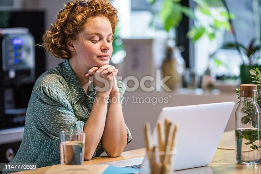 Young freelance worker reading an e-mail on a computer and thinking of something.