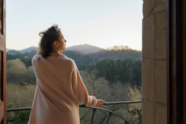 nachdenklich entspannte mädchen denken auf dem balkon. - hotel in den bergen stock-fotos und bilder