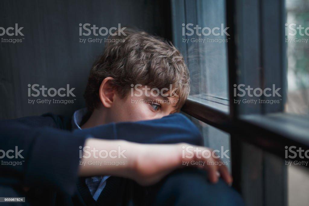 Fundersam ledsen pojke tonåring i en blå skjorta och jeans som sitter vid fönstret och stänger sitt ansikte med händerna. - Royaltyfri Allvarlig Bildbanksbilder