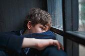 ブルーのシャツとジーンズの窓際に座って物思いに沈んだ悲しい少年ティーネー ジャー、彼の手で彼の顔を閉じます。