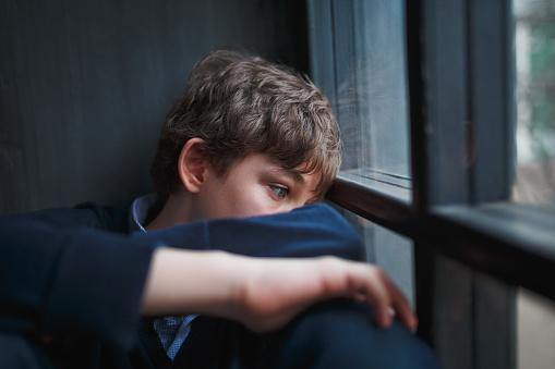 Fundersam Ledsen Pojke Tonåring I En Blå Skjorta Och Jeans Som Sitter Vid Fönstret Och Stänger Sitt Ansikte Med Händerna-foton och fler bilder på Allvarlig