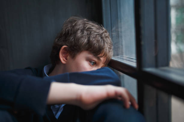 pensive sad boy teenager in a blue shirt and jeans sitting at the window and closes his face with his hands. - ragazzi adolescenti foto e immagini stock